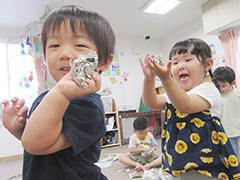 しゃがんで小石を触る園児の写真
